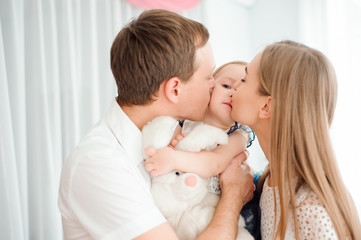 Lovely family smiling and laughing, posing at camera, and huggin