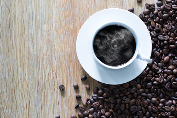 White coffee cup and pile of coffee seeds on brown wooden plate / top view and select focus