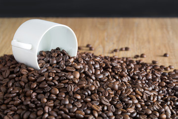 White cup on the pile of coffee seeds on brown wooden plate
