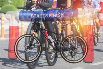 Double exposure mountain bicycle and inflatable start - finish arch with cyclists during bicycle sport racing competition background