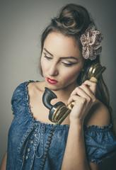 Glamorous woman using retro telephone