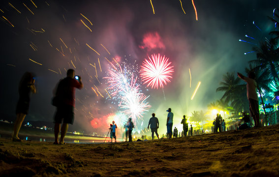 Colorful fireworks on the beach, New Year celebration in Phuket, Thailand. People on the front are de-focused, blurred and not recognizable.