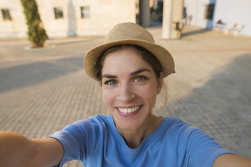 End result selfie picture of a beautiful young woman smiling, while wearing a hat and a blue tshirt