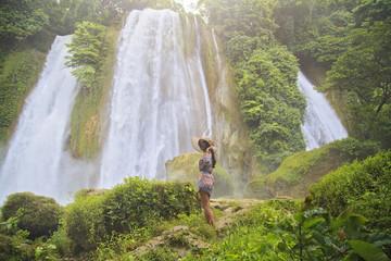 Young woman enjoying nature at Cikaso Waterfall