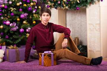 Happy young man carries a lot of gifts near the Christmas tree winter New year
