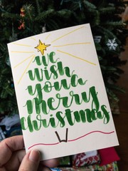 Hand holding a homemade Christmas card in front of a tree
