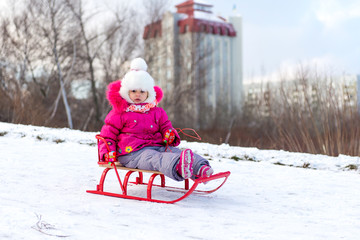 The child, a little girl riding on a sled with snow slides. Winter fun for children.
