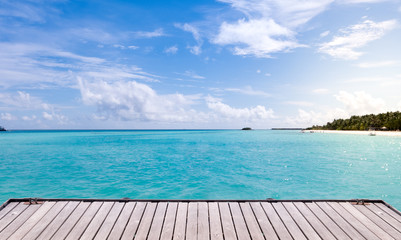 Wooden floor with sea and blue sky background.