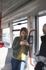 Beautiful young woman standing in tram and doing something on her cell phone.