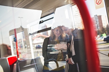 Two beautiful young women standing in tram and talking. Photo is captured from outside through window glass.