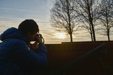 Young boy traveler photographing the sky of Brno City, Czech Republic, Europe at sunset