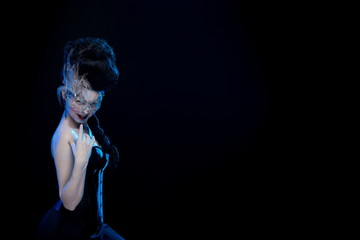 brunette woman with high hair, a mask with feathers and corset in old style on a black background