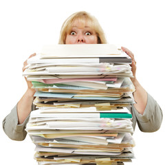 Mature woman almost buried by a mountain of paperwork