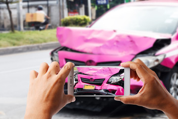 Close up hand holding smartphone and view photo of pink car accident