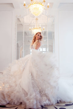 Young beautiful bride in luxurious wedding dress. Huge puffy skirt with train.