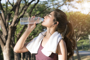 young asian woman thirsty and drinking pure water after jogging