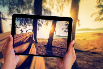 Human hand take picture with tablet of feet sleeping on swing at the sunset beach background.
