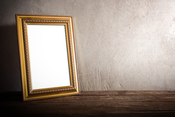 luxurious photo frame on wooden table over grunge background