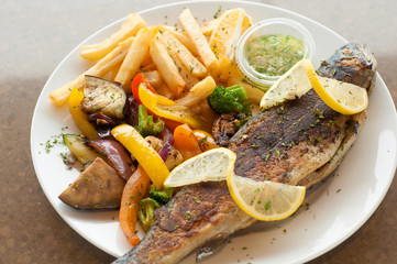 Grilled trout on a plate with grilled vegetables