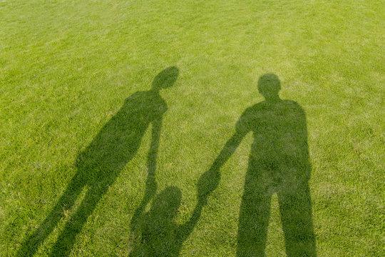 幼児と手を繋ぐ3人の影、家族のイメージ