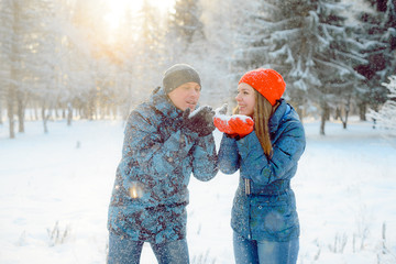 happy and beautiful young couple, a girl and a young man are walking in the frosty winter the Park playing with the snow, blow snow with it.