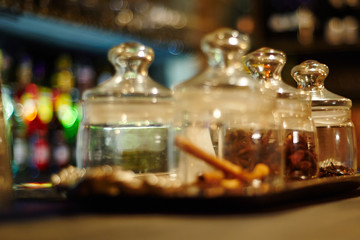 Glass with aromatic spices. Bar in the background, out of focus.