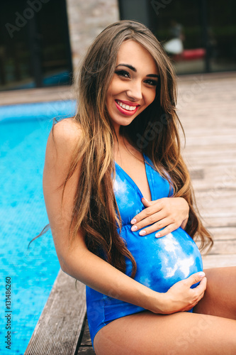 22479738f76da Beautiful pregnant woman relaxing near the blue pool in a swimsu ...
