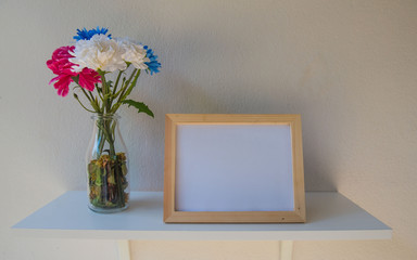 photo Frame on a wooden and Flowers in jar on White background .