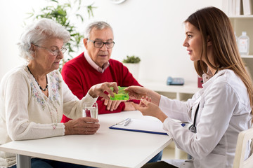 Doctor offering pills senior couple