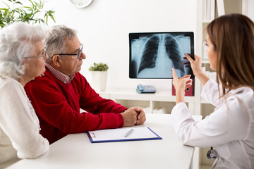 Doctor shows results to old patient x-ray of the lungs