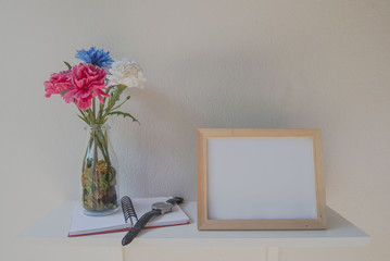 photo Frame on a wooden and Flowers in jar ,book on White background .
