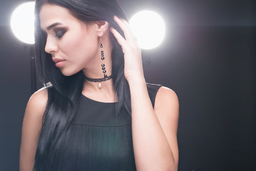 Beauty shot of brunette luxury model in dark dress and jewelry on dark background