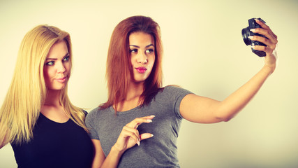 Two models girls taking self picture with camera