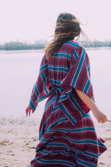 beautiful hippie girl walking near the shore girl in a dress, co