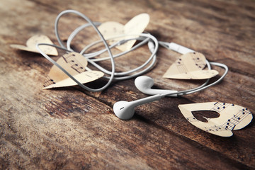 Paper hearts with music notes and earphones on wooden background