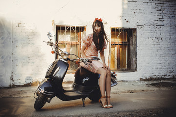 beautiful and fashionable woman on a scooter