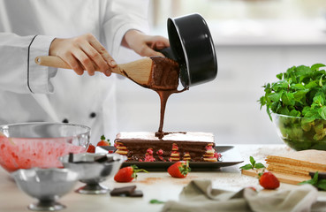 Cooking concept. Professional confectioner decorating delicious cake with chocolate frosting, closeup