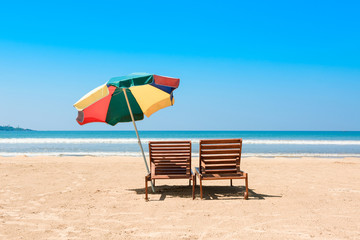 Two beach chairs and umberella on tropical ocean beach at sunny day
