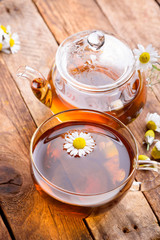 Herbal tea in cup and glass teapot with fresh chamomile herb flowers on vintage wooden table background