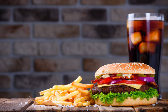 Delicious fresh hamburger with french fries and cola on wooden table