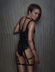Back view of sensual woman wearing black bodysuit with leather belts looking at the camera over shoulder while posing isolated on  concrete wall background