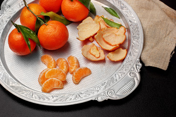 Fresh tangerine clementine with leaves in silver tray on dark stone background, top view.copy space .Selective focus
