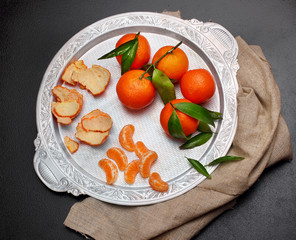 Still life.Fresh tangerine clementine with leaves in silver tray on dark stone background, top view