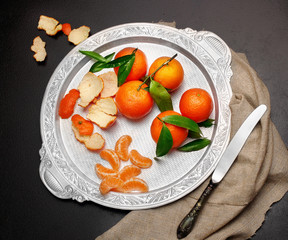 Still life.Fresh tangerine clementine with leaves in silver tray on dark stone background, with knife top view