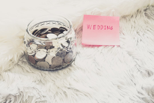 many coins in a money jar with wedding label on jar