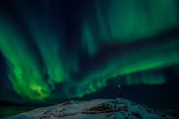 Radio tower on the hill and the Northern lights over the fjord i