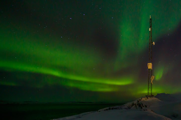 Communication tower and northern lights with a fjord in the back
