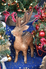 A little deer surrounded by colorful toys and Christmas trees.