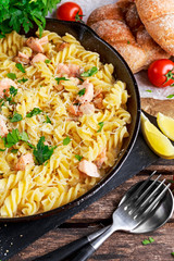 Home made Tasty Pasta with Salmon, mushrooms, lemon, herbs and cheese in rustic pan
