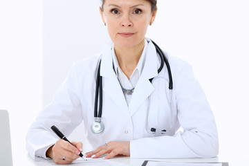 Female doctor at the table and filling up medical form. Medicine and health care concept.